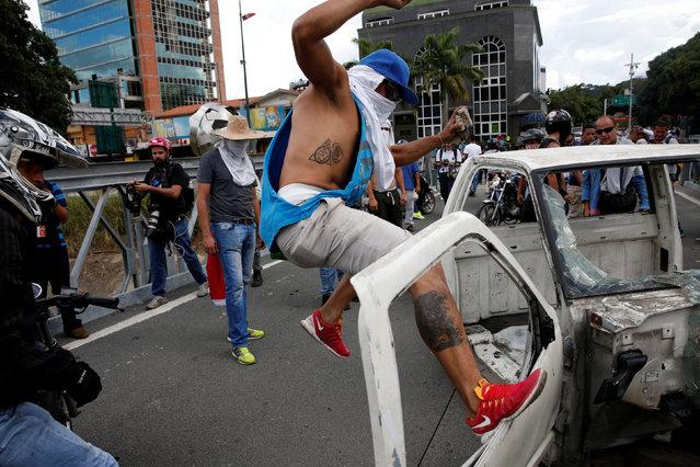 A protester tries to break apart a car during a rally to demand a referendum to remove Venezuela's President Nicolas Maduro in Caracas, Venezuela, September 1, 2016. (Photo by Carlos Garcia Rawlins/Reuters)