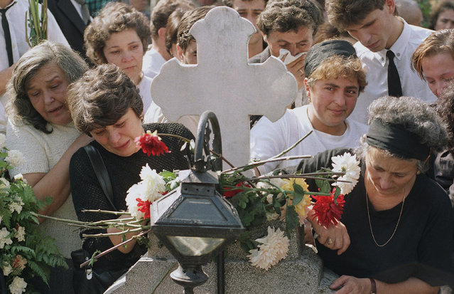 Mourners gather at the grave of Andrei Frumusanu, a 23-year-old engineering student, during his funeral in Bucharest, Saturday, September 28, 1991. The student was killed during anti-government riots sparked by miners protests. (Photo by Steven Senne/AP Photo)