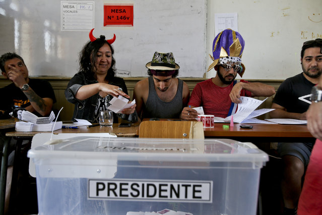 Electoral workers sport costumes during the presidential runoff election in Santiago, Chile, Sunday, December 17, 2017. Chileans will decide Sunday whether to swing the world's top copper-producing country to the right or maintain its center-left path in a fiercely contested election. (Photo by Esteban Felix/AP Photo)