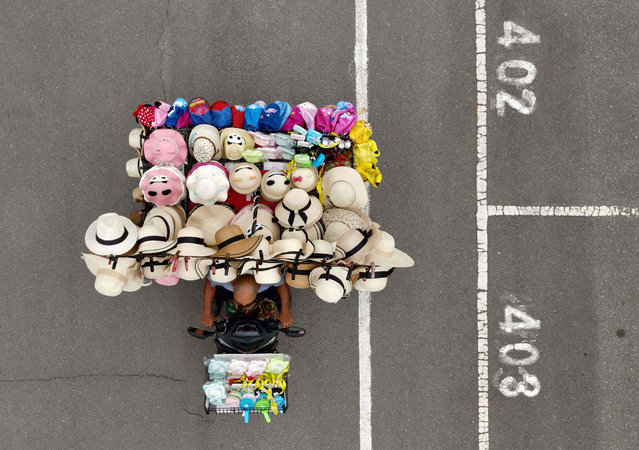 An aerial view shows Wang Shang-chi, 75, a mobile hats vender, riding his bike at a parking lot next to the Taipei City Zoo on July 9, 2020. (Photo by Sam Yeh/AFP Photo)