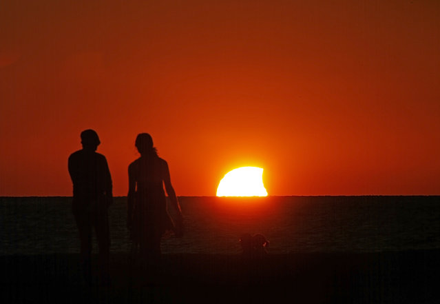 The setting and partially eclipsed sun drops below the horizon over the Gulf of Mexico off Sand Key in Clearwater, Fla., Thursday, October 23, 2014, the moon passed in front of the sun causing a partial solar eclipse. (Photo by Jim Damaske/AP Photo/Tampa Bay Times)
