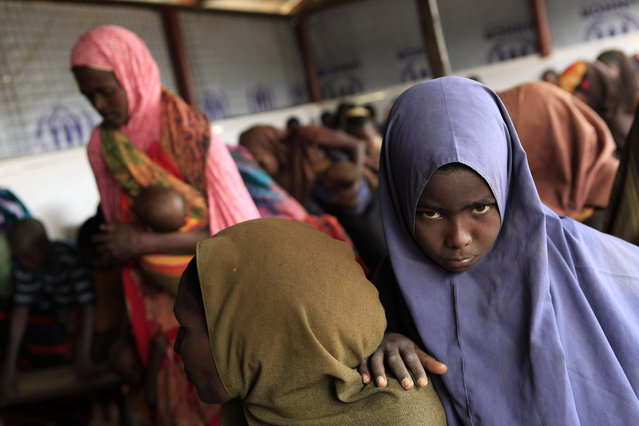 Recently-arrived Somali refugees wait to be registered at a reception center at Dagahaley Camp, outside Dadaab, Kenya, Sunday, July 10, 2011. (Photo by Rebecca Blackwell/AP Photo)