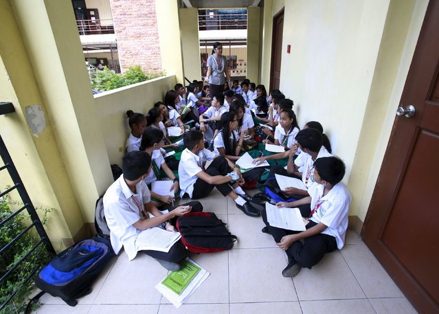 Teacher Kristine Passag holds a Values Education class for Grade 9 students in a hallway of Timoteo Paez High School in metro Manila, Philippines, September 15, 2015. Passag says she is temporarily holding classes in hallways while waiting for the completion of a new school building to address the shortage of classrooms. (Photo by Romeo Ranoco/Reuters)