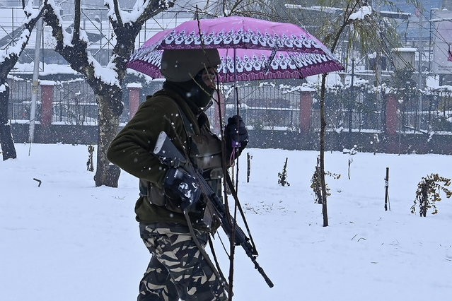 An Indian paramilitary trooper carries an umbrella as he walks through a park during snowfall in Srinagar on December 13, 2019. (Photo by Tauseef Mustafa/AFP Photo)