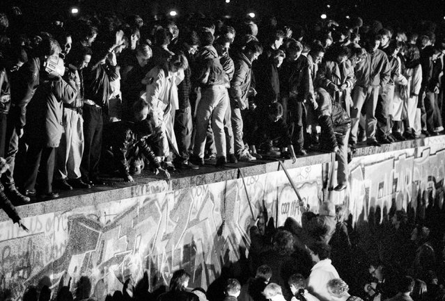 East and West German citizens celebrate as they climb the Berlin wall at the Brandenburg gate, November 9, 1989. (Photo by Fabrizio Bensch/Reuters)
