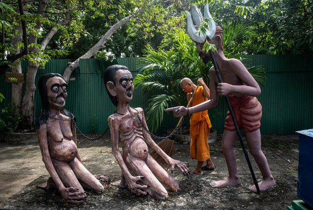 A Buddhist monk sweeps around statues illustrating the fate of people who do bad deeds in a garden depicting a Buddhist version of hell at the Wat Saeng Suk temple in the Thai coastal province of Chonburi on July 9, 2020. (Photo by Lillian Suwanrumpha/AFP Photo)
