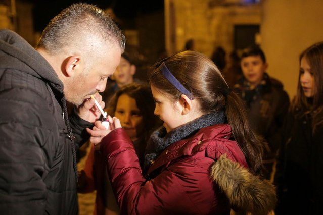 Luisa Ines, 10-years-old, gets her father Carlos Cadavez, a non-smoker, to help her light a cigarette in the village of Vale de Salgueiro, northern Portugal, during the local Kings' Feast Friday night, January 5, 2018. (Photo by Armando Franca/AP Photo)