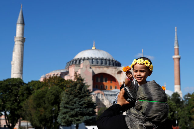 A woman holds a child in front of Hagia Sophia or Ayasofya-i Kebir Camii in Istanbul, Turkey, July 23, 2020. (Photo by Murad Sezer/Reuters)