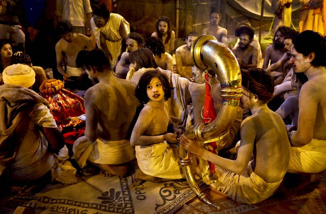 A young Naga sadhu or naked Hindu holy man sits with others during an evening prayer at their camp at Sangam for the Maha Kumbh festival, in Allahabad, India, on February 7, 2013. (Photo by Manish Swarup/Associated Press)