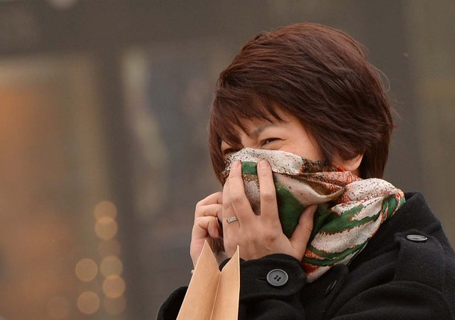 """A Chinese woman tries to protect herself as Beijing is hit by a sandstorm as well as air quality worse than the highest classification of """"hazardous"""" on February 28, 2013. State media reported that Beijing air pollution levels reached extremely hazardous levels for the second time this week as citizens struggled to protect themselves from the two-pronged hazards of dust and pollution. (Photo by Mark Ralston/AFP Photo)"""