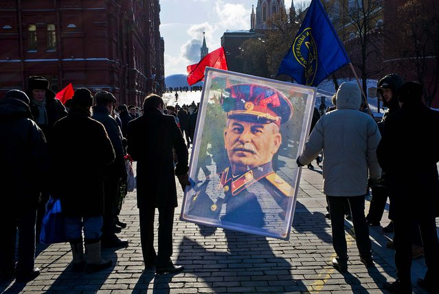 Communist supporters carry a portrait of former Soviet dictator Josef Stalin as they line up to place flowers on Stalin's grave in Red Square to mark the 60th anniversary of his death, on March 5, 2013. (Photo by Alexander Zemlianichenko/Associated Press)