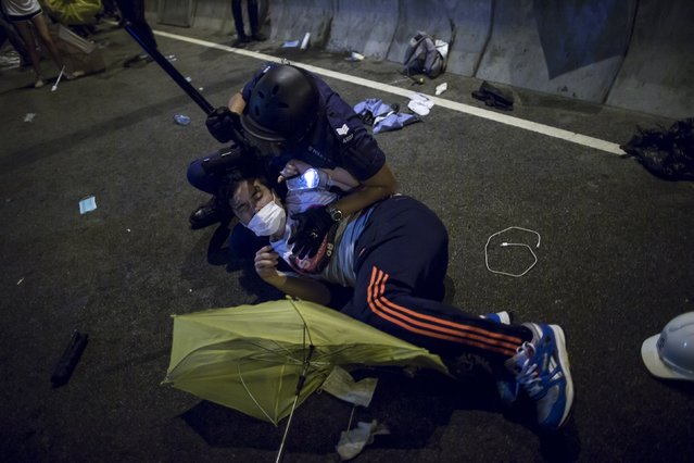 A riot policeman detains a pro-democracy protester close to the chief executive office in Hong Kong December 1, 2014. (Photo by Tyrone Siu/Reuters)