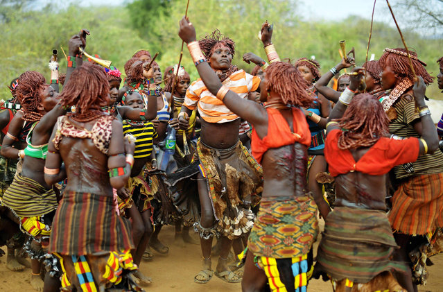 "Hamar women dance before a bull jumping ceremony in Ethiopia's southern Omo Valley region near Turmi on September 19, 2016. The Hamar are a Nilotic ethnic group in Ethiopia. The construction of the Gibe III dam, the third largest hydroelectric plant in Africa, and large areas of very ""thirsty"" cotton and sugar plantations and factories along the Omo river are impacting heavily on the lives of tribes living in the Omo Valley who depend on the river for their survival and way of life. Human rights groups fear for the future of the tribes if they are forced to scatter, give up traditional ways through loss of land or ability to keep cattle as globalisation and development increases. (Photo by Carl De Souza/AFP Photo)"