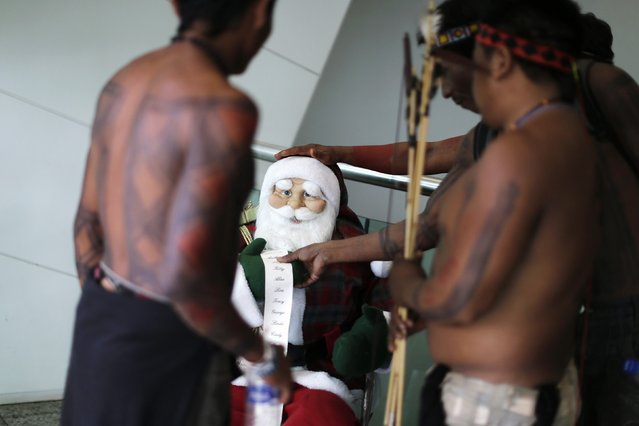 Indigenous men look at a Santa Claus doll at the entrance of the building of the National Confederation of Agriculture building during a protest against the approval of the Proposed Constitutional Amendment (PEC 215) in Brasilia December 5, 2014. Indigenous protesters are demonstrating against the possible appointment of Senator Katia Abreu to the Ministry of Agriculture in Brasilia. (Photo by Ueslei Marcelino/Reuters)