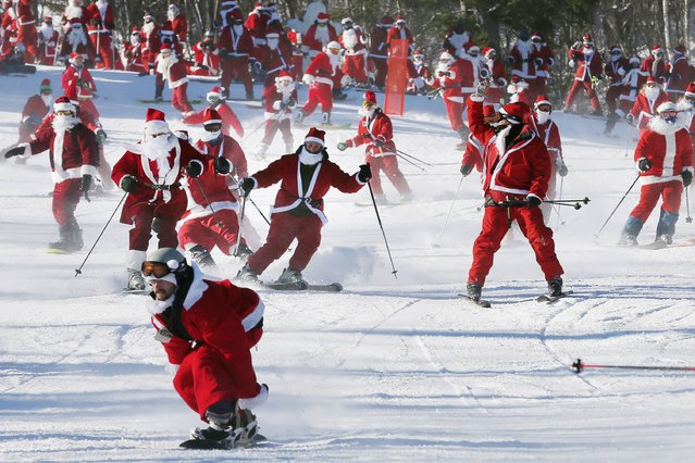 Skiers and snowboarders dressed as Santa participate in a charity run down a slope at Sunday River Ski Resort in Newry, Maine December 7, 2014. (Photo by Brian Snyder/Reuters)