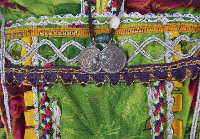 A woman cotton picker wears pendants, each featuring Allah and the Hindu deity Hanuman, in Meeran Pur village, north of Karachi November 23, 2014. (Photo by Akhtar Soomro/Reuters)