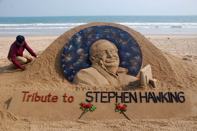 """Sand artist Sudarsan Patnaik gives final touches to a sculpture in honour of British physicist and award-winning author Stephen Hawking at Puri beach, some 65 kms. from Bhubaneswar on March 14, 2018. Renowned British physicist Stephen Hawking, whose mental genius and physical disability made him a household name and inspiration across the globe, died on March 14th aged 76. Propelled to superstardom by his 1988 book """"A Brief History of Time"""", which became an unlikely worldwide bestseller, Hawking dedicated his life to unlocking the secrets of the Universe. (Photo by Asit Kumar/AFP Photo)"""