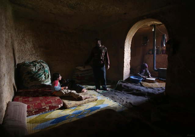 Sami (center) speaks with his children in an underground Roman tomb which he uses with his family as shelter from Syrian government forces, at Jabal al-Zaweya, in Idlib province, on February 28, 2013. The ancient sites are built of thick stone that has already withstood centuries, and are often located in strategic locations overlooking towns and roads. (Photo by Hussein Malla/AP Photo /The Atlantic)