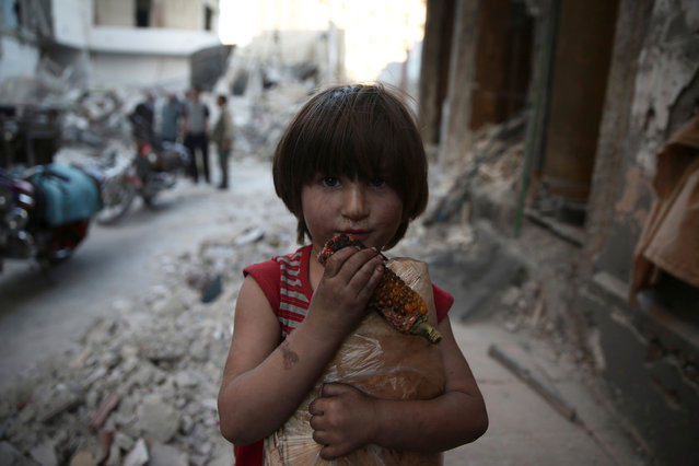 A child eats a corn comb while carrying a bag of bread in a damaged site after an airstrike yesterday in the rebel held Douma neighbourhood of Damascus, Syria October 4, 2016. (Photo by Bassam Khabieh/Reuters)