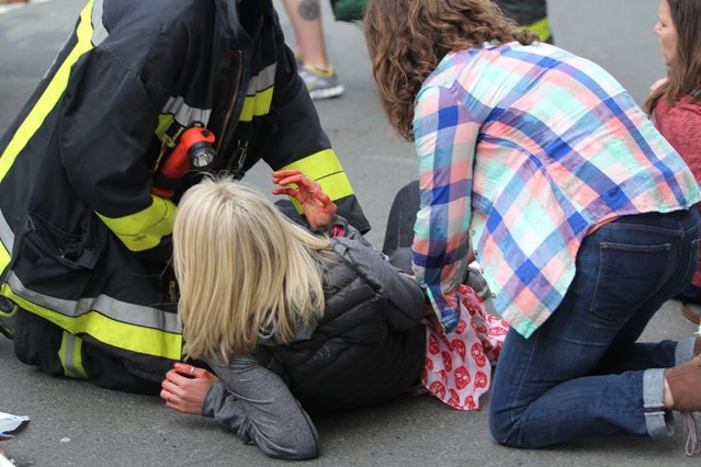 An injured woman is attended to at the scene of an explosion at the Boston Marathon in Boston, Massachusetts, April 15, 2013. (Photo by Kenshin Okubo/Reuters/Daily Free Press/Boston University)