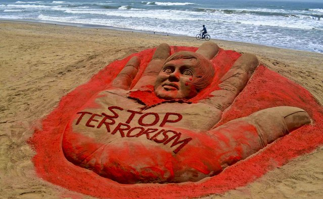 A cyclist pedals past a sculpture at the golden sea beach in Puri, India, with a message against terrorism following attacks in Boston and Bangalore, on April 17, 2013. (Photo by Associated Press)