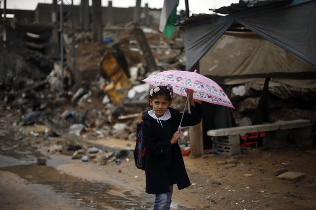 A Palestinian school girl holds an umbrella as she walks near the ruins of houses that witnesses said were destroyed by Israeli shelling during the most recent conflict between Israel and Hamas, on a rainy day in the east of Gaza City November 24, 2014. (Photo by Suhaib Salem/Reuters)