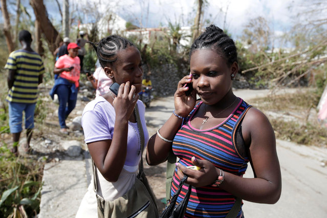 People check for cellular signals after Hurricane Matthew passed, in Camp Perrin, Haiti, October 8, 2016. (Photo by Andres Martinez Casares/Reuters)