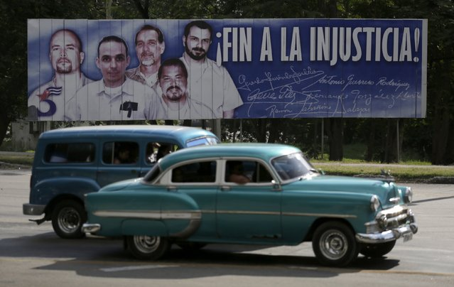 Cars drive past a banner featuring five Cuban prisoners held in U.S. custody, two of whom were previously released, in Havana December 17, 2014. U.S. President Barack Obama was set to announce a shift in policy toward Cuba on Wednesday and the Associated Press reported the changes would include the opening of an embassy in Cuba and the start of talks to normalize relations. (Photo by Enrique De La Osa/Reuters)