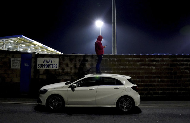 Fans stand atop a car to look over the boundary wall, watching the action during the English FA Cup first round match Barrow against Wimbledon, at the Progression Solicitors Stadium in Barrow, England, Thursday November 26, 2020. (Photo by Zac Goodwin/PA Wire via AP Photo)