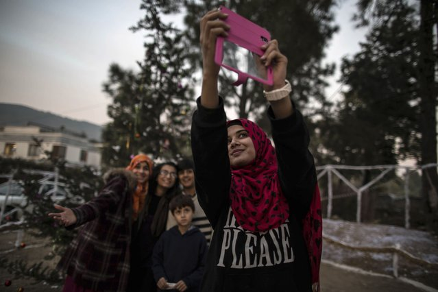 Muslims take a selfie near a Christmas tree ahead of Christmas in a Christian slum in Islamabad December 24, 2014. (Photo by Zohra Bensemra/Reuters)