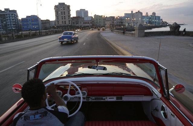 Michel Salgado drives his 1957 Mercury Monterrey convertible car along the Malecon in Havana, Cuba, Sunday December 21, 2014. (Photo by Desmond Boylan/AP Photo)