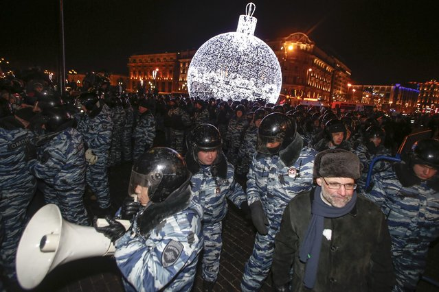 Police prepare to push supporters of Russian opposition activist and anti-corruption crusader Alexei Navalny away during an unsanctioned protest in Manezhnaya Square in Moscow, Russia, Tuesday, December 30, 2014. (Photo by Denis Tyrin/AP Photo)