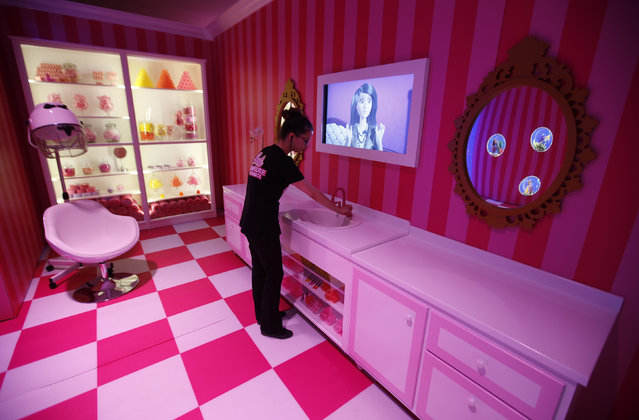 """A staff poses for the photographer inside a life-size """"Barbie Dreamhouse"""" of Mattel's barbie dolls in the bathroom during a media tour in Berlin, May 15, 2013. (Photo by Fabrizio Bensch/Reuters)"""