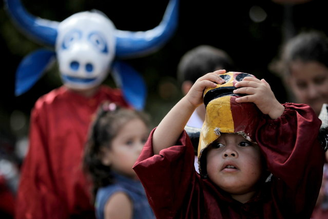 """A child looks out from under his mask during the """"Cavalhadas"""" festival in Pirenopolis, Brazil, Sunday, May 19, 2013. The popular festival, featuring masked horsemen, is a tradition that was introduced in the 1800's by a Portuguese priest to mark the the ascension of Christ. The 3-day festival reenacts the Christian knights' medieval defeat of the Moors. (Photo by Eraldo Peres/AP Photo)"""