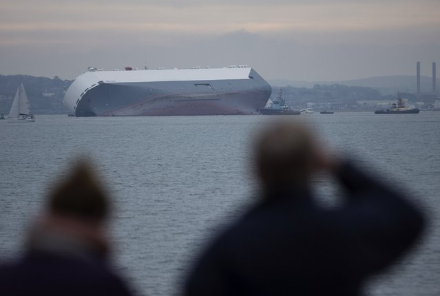 People look out towards the cargo ship Hoegh Osaka as it lies on its side after running aground on Saturday evening in the Solent estuary, near Southampton in southern England, January 4, 2015. (Photo by Peter Nicholls/Reuters)