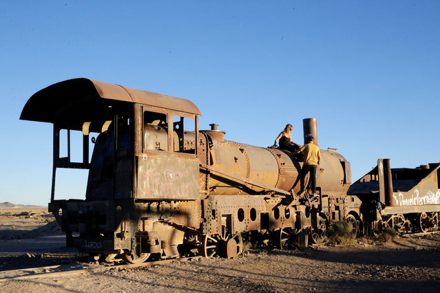 A couple are seen on a locomotive of Bolivian Railways Company from 1870-1900 at the train cemetery in Uyuni, Potosi, Bolivia on May 16, 2018. (Photo by David Mercado/Reuters)