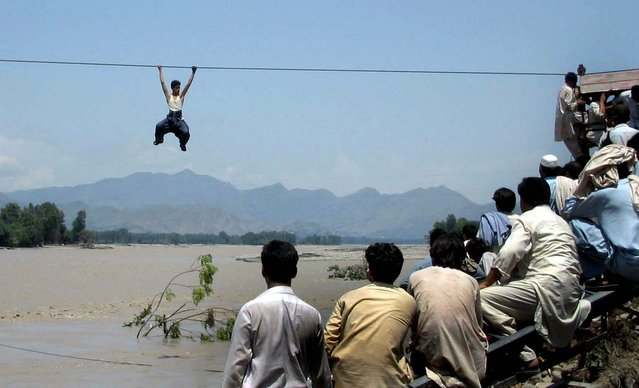Onlookers perched on a damaged bridge watch a flood survivor climb a rope to cross the river in Pakistan's Swat Valley's Chakdara on August 3, 2010. (Photo by AFP Photo)