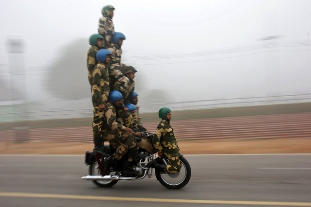 "India's Border Security Force (BSF) ""Daredevils"" motorcycle riders perform during a rehearsal for the Republic Day parade on a foggy winter morning in New Delhi January 8, 2015. (Photo by Ahmad Masood/Reuters)"