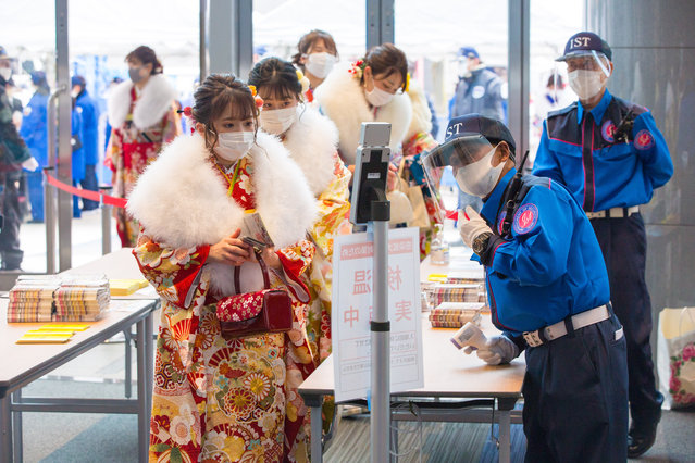 "A participant wearing traditional clothes is taken through a body temperature scan before being allowed to enter the event hall in Yokohama, Japan on January 11, 2021. The Coming of Age ceremony is an important Japanese traditional holiday also called ""Seijin no hi"", to celebrate the change from childhood to adulthood. Due to Covid-19 pandemic, several measures have been set in place to contain the spread of the virus, such as mandatory facemask, body temperature control, hand sanitizer. Police also arrested several drunk young men as they tend to drink a lot during this ceremony. (Photo by Stanislav Kogiku/SOPA Images/Rex Features/Shutterstock)"