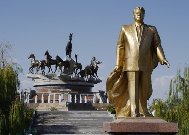 """One of many golden statues of Saparmurat Niyazov, former President for Life of Turkmenistan, with native Akhal-Teke horses depicted atop a monument marking 10 years of independence. The hardy desert horse is Turkmenistan's national symbol, and a passion of the current president, Gurbanguly Berdimuhamedow. In his book The Flight of Celestial Racehorse, Berdimuhamedow aligns himself with the noble Akhal-Teke breed in one of the more bizarre quotes from the book: """"Riding on horse, driving plane steering wheel, sea liner, driving powerful (truck), Gurbanguly Berdimuhamedov not just demonstrates wonderful physical shape and high professional skills in every business, he fixes in people's minds the image of modern (strongman), who has to do a lot. He must be well-educated, physically strong and esthetically erudite"""". Unfortunately for Berdimuhamedow, a festival to celebrate the horses earlier this year ended with the president taking a spectacular fall which was shared widely on YouTube. (Photo by Amos Chapple via The Atlantic)"""