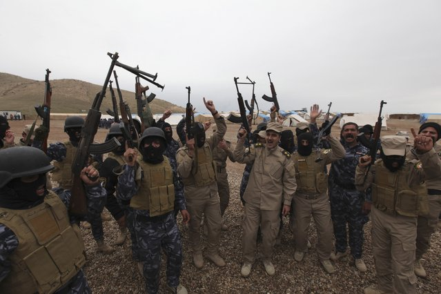 Members of Iraqi security forces chant slogans during training, as they prepare to fight against militants of the Islamic State, at a training camp on the outskirts of Mosul January 10, 2015. (Photo by Azad Lashkari/Reuters)