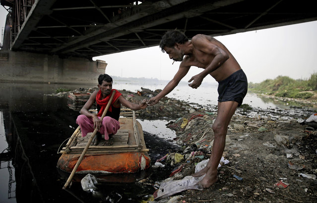 In this photo taken May 28, 2018, Ram Nath, 40, left, who makes a living from recycling trash, receives a bidi from another garbage collector, before going out to look for plastic bottles and other reusable trash through murky waters of Yamuna, India's sacred river that flows through the capital of New Delhi. For more than 25 years, Ram Nath has lived on the banks of the Yamuna River under a 19th-century iron bridge. Each morning, the wiry man walks a few steps from his makeshift hut and enters the black, sludgy waters of one of India's most polluted rivers. (Photo by Altaf Qadri/AP Photo)