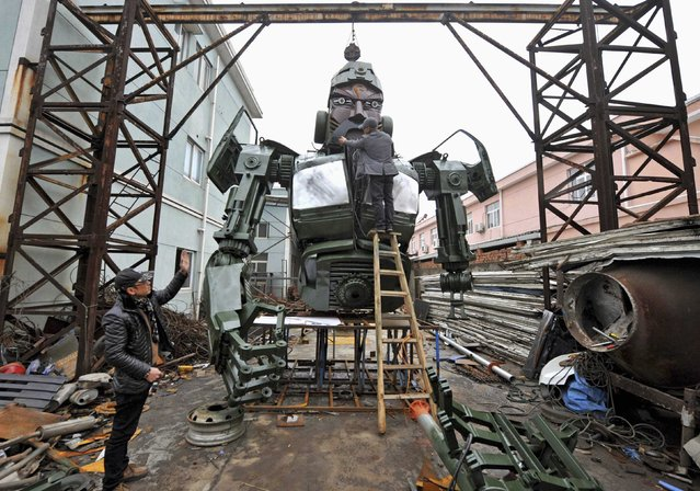 "Wang Rong (L) talks to Zhou Zefu as they make a giant steel sculpture of Guan Yu, known also as ""Guan Gong"", a famous historical character in the Three Kingdoms period, at an open air workshop in Ningbo, Zhejiang province January 14, 2015. Automobile repairing garage owner Wang and his partners, professional welders Zhou and Shen Xinxing (not pictured) share an enthusiasm for making a giant steel sculpture. (Photo by Reuters/China Daily)"