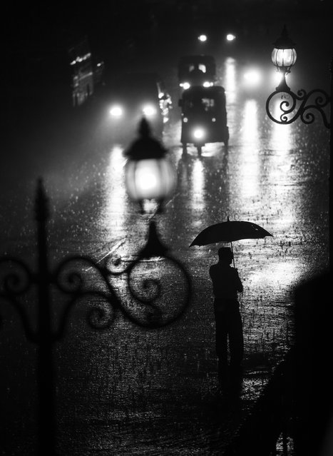 """In the middle of the pouring rain"". The picture has been taken in Kandy in Sri Lanka. We found a shelter just before the monsoon rain and watched the streets. (Photo and caption by Bartlomiej Mielnik/National Geographic Traveler Photo Contest)"