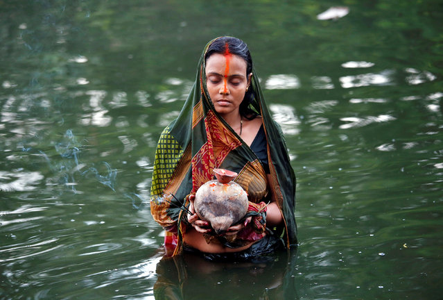 A Hindu devotee holds offerings as she worships the Sun God in the waters of a pond during the religious festival of Chhat Puja in Kolkata, November 7, 2016. (Photo by Rupak De Chowdhuri/Reuters)