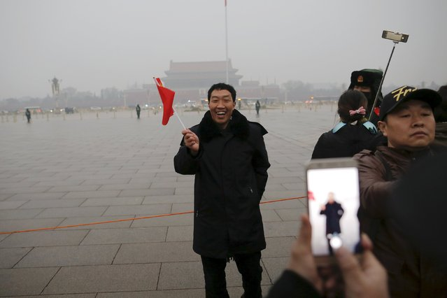 "A man smiles as his picture is taken just after a flag-raising ceremony amid heavy smog at the Tiananmen Square, after the city issued its first ever ""red alert"" for air pollution, in Beijing December 9, 2015. (Photo by Damir Sagolj/Reuters)"
