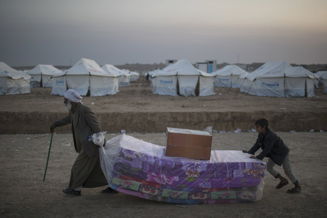 Iraqis displaced by fighting in Mosul carries mattresses at a camp for internally displaced people in Hassan Sham, Iraq, on Tuesday, November 8, 2016. The United Nations says over 34,000 people have been displaced from Mosul, with about three quarters settled in camps and the rest in host communities. (Photo by Felipe Dana/AP Photo)