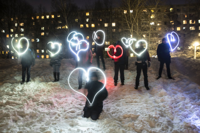People draw hearts with their cellphones flashlights in support of jailed opposition leader Alexei Navalny and his wife Yulia Navalnaya Moscow, Russia, Sunday, February 14, 2021. When the team of jailed Russia opposition leader Alexei Navalny announced a protest in a new format, urging people to come out to their residential courtyards on Sunday and shine their cellphone flashlights, many responded with jokes and skepticism. After two weekends of nationwide demonstrations, the new protest format looked to some like a retreat. But not to Russian authorities, who moved vigorously to extinguish the illuminated protests planned for Sunday. (Photo by Pavel Golovkin/AP Photo)