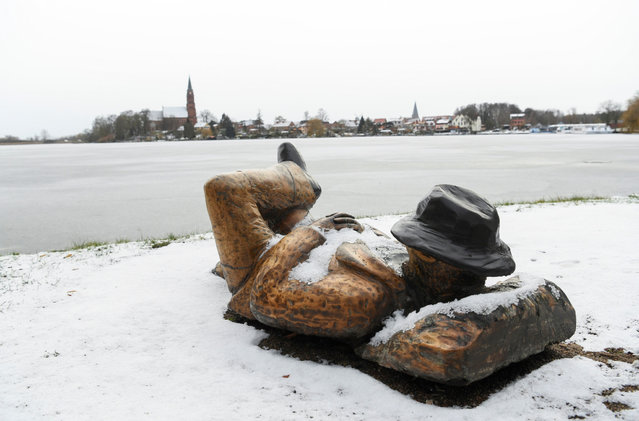 A snow-covered wooden sculpture is seen at the waterfront of lake Mueritz, in Roebel, Germany, February 4, 2021. (Photo by Annegret Hilse/Reuters)