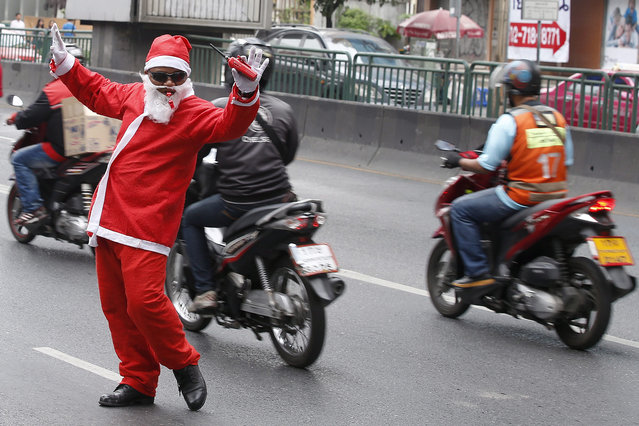 A Thai traffic security guard wears a Santa Claus costume as he directs the traffic on a street during Christmas celebrations outside a shopping mall in Bangkok, Thailand, 22 December 2011. The campaign of a shopping mall is held to celebrate the upcoming Christmas season and to attract shoppers. (Photo by Narong Sangnak/EPA)